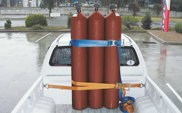 Three acetylene gas cylinders safely secured in the back of an open-back vehicle