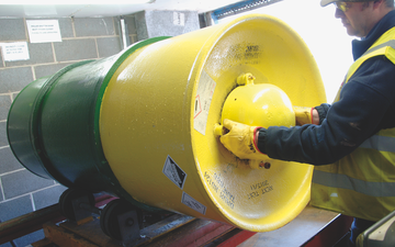 An employee safely rolling a drum of sulphur dioxide