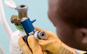 Operating theatre technician inspecting a medical oxygen cylinder