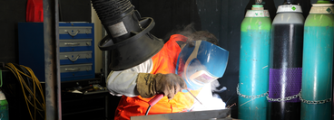 A welder wearing safety equipment demonstrating welding