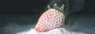 a strawberry that has been frozen and contains a frosting of ice