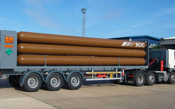 A BOC truck delivering helium gas in bulk tubes on a trailer