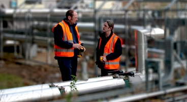 2 men in high vis waistcoats outside a plant looking at pipes.