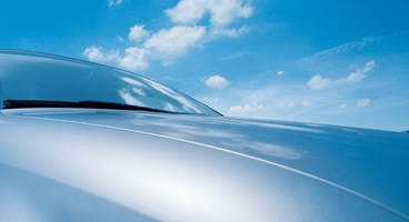 View over car hood with blue sky and clouds