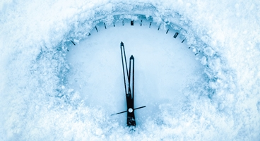 A clock face half covered underneath some snow and ice