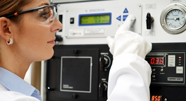 Laboratory technician wearing PPE adjusts the capacity analyser for moisture