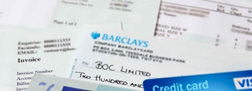 Picture showing money, credit card, bills, invoices and a cheque made payable to BOC Limited.