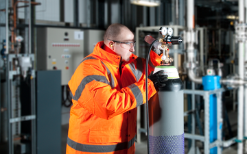 An engineer wearing an orange high viz jacket inspecting an industrial gas cylinder