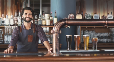 Man working in a bar serving beers and soft drinks